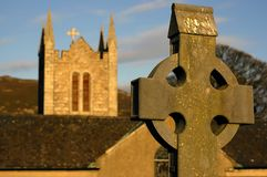 Celtic cross with the church. In the background in Ireland Stock Photo