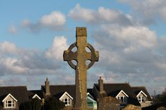 Celtic Cross in foreground with houses and blue sky in back. Celtic Cross at Cemetery in Kilkenny, Ireland, with houses in background. Blue sky with grey clouds Royalty Free Stock Images