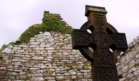 Celtic cross in an Irish cemetery 03. Celtic cross in an Irish cemetery with church ruins in the background royalty free stock image