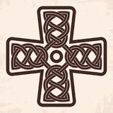 Celtic national cross. Celtic cross with national ornament as interlaced. Old beige background with the aging effect Stock Photography