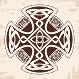 Celtic national cross. Celtic cross with national ornament as interlaced ribbon. Old brown background with the aging effect Royalty Free Stock Photo