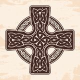 Celtic national cross. Celtic cross with national ornament as interlaced ribbon. Old brown background with the aging effect Stock Image