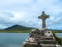 Celtic Cross over looking Mountain and Water. This is an ancient Celtic Cross overlooking the Achill Sound and mountain in the background. It is situated at The stock photography