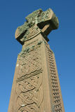 Celtic cross (Portrait). A moss covered celtic cross against a clear blue sky Stock Photo