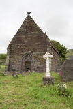 Celtic cross and ruin of a church, Ireland Royalty Free Stock Photos