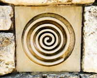 Celtic or goddess symbol. Ceramic tile in old rock wall with a spiral sign, a celtic religious symbol also used by goddess worshippers and in wicca or pagan Royalty Free Stock Photography