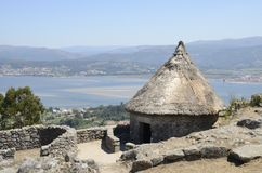 Celtic house and the Minho Estaury. One of the reconstructed houses in the remains of a celtic settlement in Santa Tecla Mount in Galicia, Spain with views to stock photo
