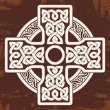 Celtic national cross. Celtic cross with national ornament as interlaced ribbon. Old brown background with the aging effect Stock Photography