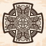 Celtic national cross. Celtic cross with national ornament as interlaced ribbon and dogs. Old brown background with the aging effect Stock Photos