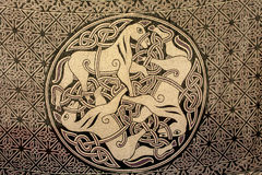 Celtic ornament of three horses on the fabric. Ancient symbol of Stock Image