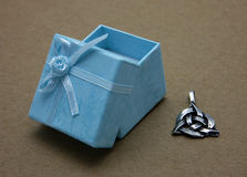 Celtic pendant and blue gift box. Silver pewter celtic knot pendant beside a light blue open gift box Royalty Free Stock Photography