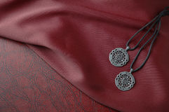 Celtic pendants on red silk cloth on leather book. Celtic pendants on leather rope on red silk cloth on leather book stock images