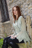 Celtic Red. Stunning redhead model posing as celtic girl in medieval town Royalty Free Stock Photos