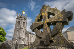 Celtic tomb and a cathedral. Celtic cross on a tomb in a cemetery in Limerick, Ireland Stock Photo
