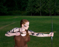 Celtic warrior girl. Beautiful redhead girl in celtic tribal makeup drawing a bow stock photography