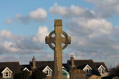 Celtycki krzyż w przedpolu z domami i niebieskie niebo w plecy Obrazy Royalty Free