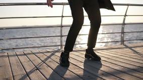 Celujący materiał filmowy samiec nogi w tanu Nowożytny hip hop wykonujący mężczyzną w czarnych sneakers z ranku morzem na zbiory