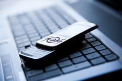 Celular en una computadora portátil fotos de archivo libres de regalías