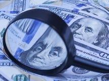 Cem cédulas do dólar sob a lupa Foto de Stock