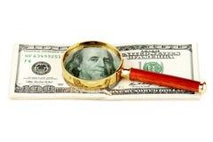 Cem contas de dólar sob uma lupa Fotografia de Stock Royalty Free