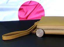 Cem moedas japonesas dos ienes no JPY reverso com a carteira da cor da areia no fundo preto do assoalho e da bandeira de Japão imagens de stock royalty free