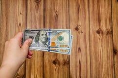 Cem notas de dólar à disposição no fundo de madeira foto de stock royalty free