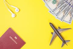 Cem notas de dólar, avião, fones de ouvido, passaporte estrangeiro no fundo de papel amarelo brilhante Copie o espaço fotografia de stock royalty free