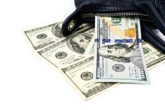 Cem notas de dólar caíram fora da obscuridade - bolsa azul das senhoras sobre imagem de stock royalty free