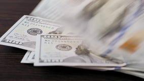 Cem notas de dólar caem em uma superfície de madeira filme