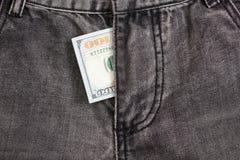 Cem notas de dólar dentro das calças de brim do cinza do codpiece Fotos de Stock Royalty Free