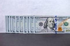 Cem notas de dólar dobradas em seguido fotos de stock