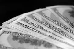 Cem notas de dólar em um fundo escuro, preto e branco Fotografia de Stock