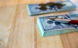 Cem notas de dólar, moedas tailandesas e pena no de madeira velho Imagem de Stock