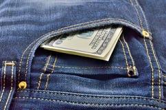 Cem notas de dólar nas calças de brim Foto de Stock Royalty Free