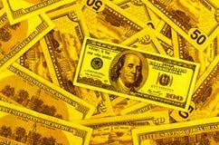 Cem notas de dólar no fundo dos dólares ouro do fundo Imagens de Stock Royalty Free