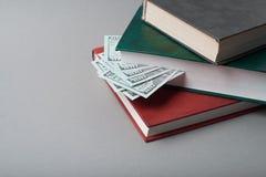 Cem notas de dólar nos livros fotografia de stock