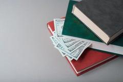 Cem notas de dólar nos livros imagem de stock
