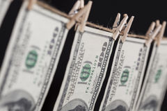 Cem notas de dólar que penduram da corda no fundo escuro Imagens de Stock Royalty Free