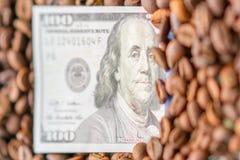 Cem notas de dólar são enchidas com os feijões de café Foco seletivo fotografia de stock royalty free