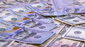 Cem quedas das notas de dólar na tabela com dólares americanos de denominações diferentes filme