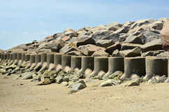 Cement Barrior Sea Wall Seawall Coastal Defense. Cement barriers lined up along the beach sand to form sea wall with large rocks piled high behind the barriers Royalty Free Stock Image