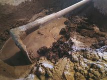 Cement die zich met schoffel in het mengen van dienblad voor bouw mengen Stock Foto
