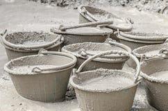 Cement die zich in plastic emmer mengen Stock Afbeeldingen