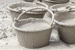 Cement die zich in plastic emmer mengen Stock Foto