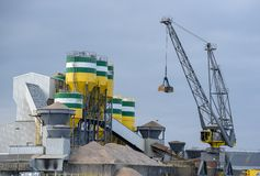 Cement factory with cranes for transporting raw materials. The silos in which the raw materials are mixed into cement and the conveyor belts are clearly stock photography