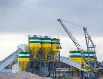 Cement factory with cranes for transporting raw materials. The silos in which the raw materials are mixed into cement and the conveyor belts are clearly stock photos