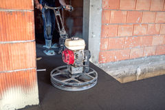Cement gladmakende en nivellerende troffelmachines met arbeider het vloeren het gladmaken bij nieuw huisbouwwerf stock afbeelding