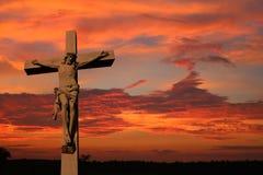 Cement life size cross with body of Jesus as sun sets. Concrete crucifix  against magnificent sunset. Easter, lent, sacrifice, atonement concept stock photo