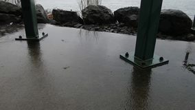 Cement and metal posts of structure in rain storm. Along puget sound stock video footage