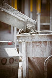 Cement mixer. Concrete and Cement getting poured out of a mixer truck in to a construction bucket at job site stock images